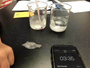 Middle school science experiment showing two beakers and a phone with a stopwatch.